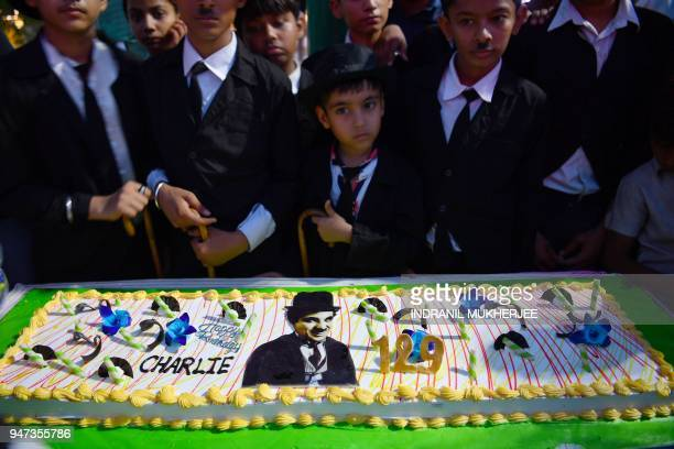 In this photograph taken on April 16 young Charlie Chaplin impersonators stand behind a cake during an event commemorating the legendary actor's...