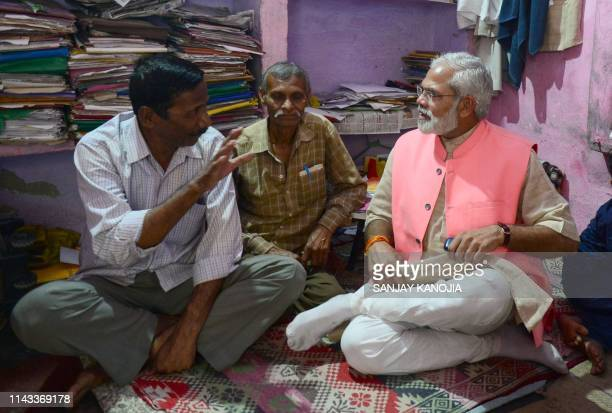 In this photograph taken on April 17 Abhinandan Pathak a lookalike of Indian Prime Minister Narendra Modi speaks with voters as he campaigns in a...