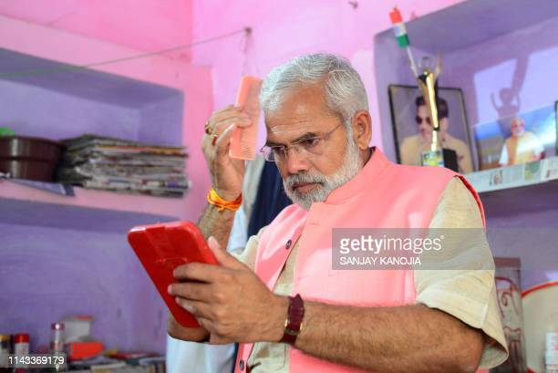 In this photograph taken on April 17 Abhinandan Pathak a lookalike of Indian Prime Minister Narendra Modi combs his hair as he campaigns in a...