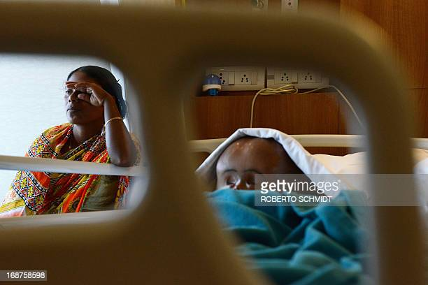 In this photograph taken on April 18 the mother of Indian child Roona Begum Fatima Khatun wipes her eyes in fatigue as she sits next to her...
