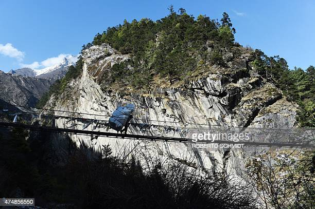 In this photograph taken on April 19 a Nepalese porter carries merchandise over a suspension bridge in Phunki in the Khumbu region The UN World Food...
