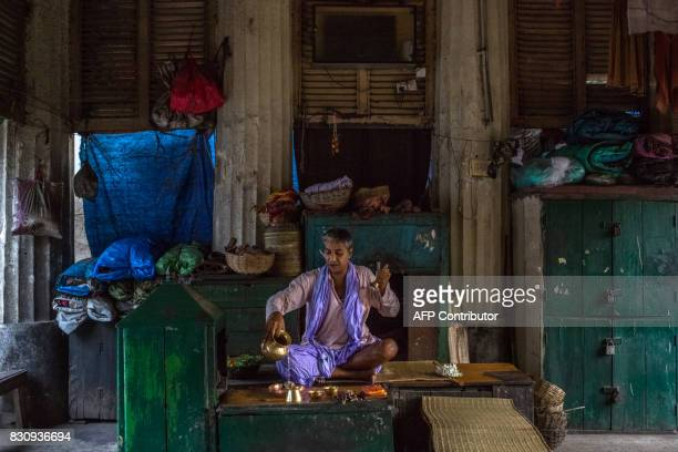 In this photograph taken on April 20 Indian Hindu priest Pandit Garhi Seelam performs a ceremony at Babughat on the banks of the Hooghly River in...