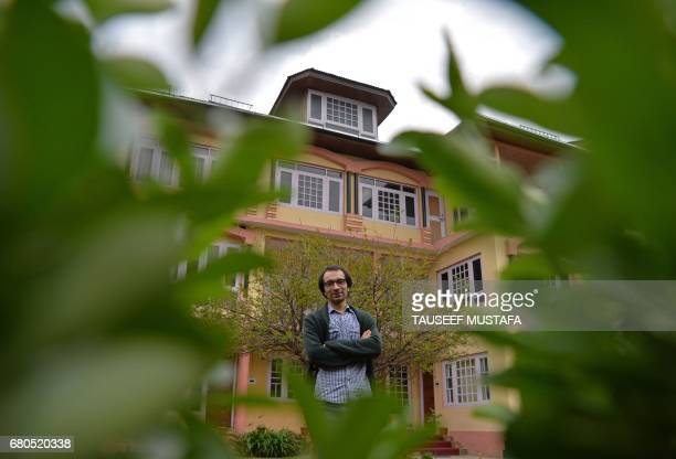 In this photograph taken on April 20 Kashmiri cartoonist Malik Sajad poses for a photograph at his home in Srinagar. - Through sombre black and white...