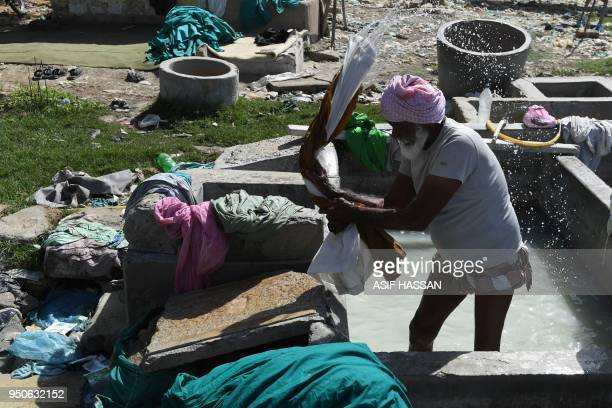 In this photograph taken on April 23 a Pakistani dhobi or laundry man beats clothes on a stone at a traditional Dhobi Ghat or openair laundry...