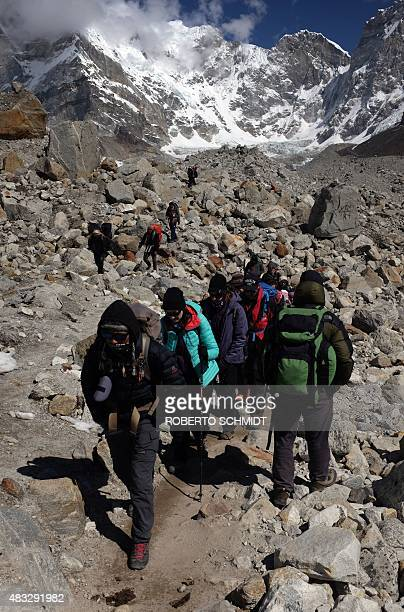 In this photograph taken on April 24 trekkers and climbers make their way up and down a trail leading to the village of Gorak Shep and Everest Base...