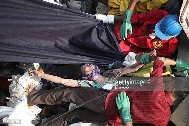 In this photograph taken on April 25 Civilians rescue an injured garment worker during a rescue operation after the eight-storey building Rana Plaza...