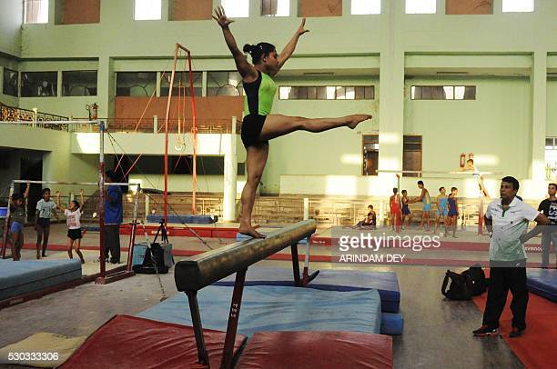 In this photograph taken on April 25 Indian gymnast Dipa Karmakar performs a pirouette as coach Bisbeshwar Nandi looks on during a practice session...