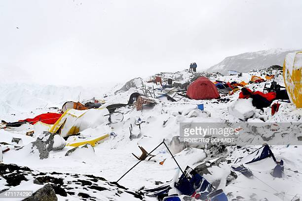 In this photograph taken on April 25 people look on at the devastation after an avalanche triggered by an earthquake flattened parts of Everest Base...