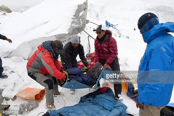 In this photograph taken on April 25 rescuers help a porter onto a makeshift stretcher after he was injured by an avalanche caused by an earthquake...