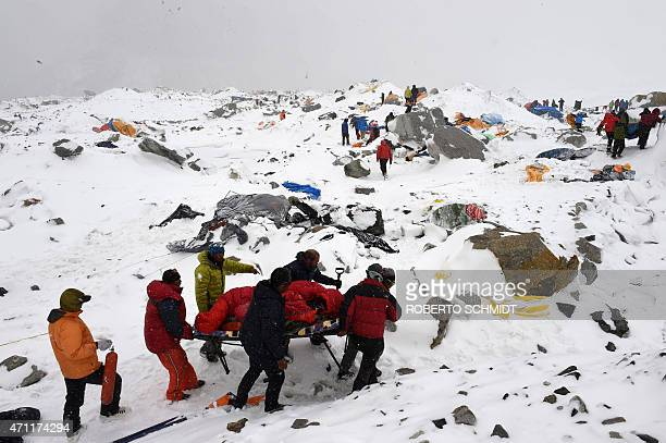 In this photograph taken on April 25 rescuers use a makeshift stretcher to carry an injured person after an avalanche triggered by an earthquake...