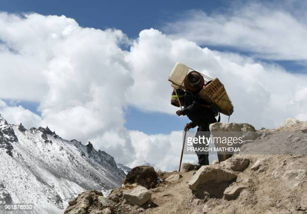 In this photograph taken on April 26 a Nepali porter carries supplies to Everest base camp some 140 kilometres northeast of Kathmandu Wifi baked...