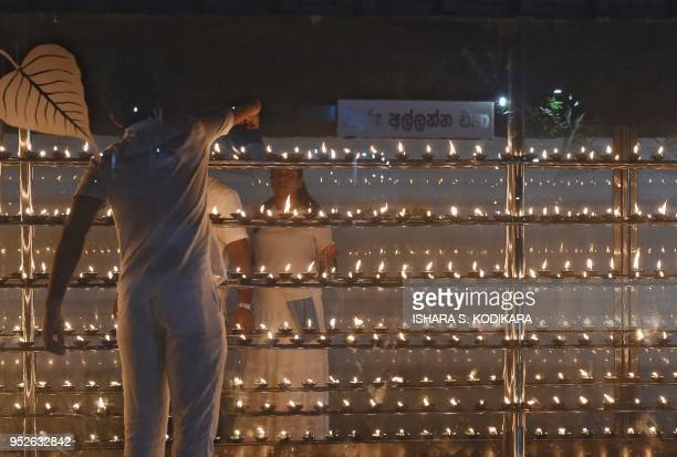 In this photograph taken on April 28 a Sri Lankan Buddhist devotee lights oil lamps during 'Vesak' festival at the Kataragama Kiriwehera temple in...
