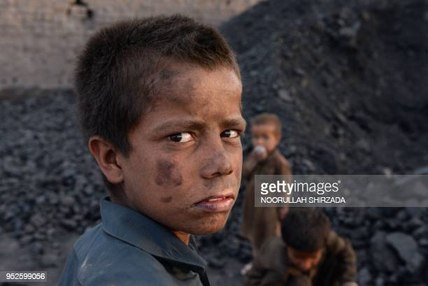 In this photograph taken on April 28 Afghan children work at a coal yard on the outskirts of Jalalabad.