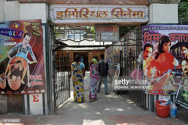 In this photograph taken on April 29 Indian patrons walk past posters at the entrance to the century old single screen theatre Imperial Cinema in...