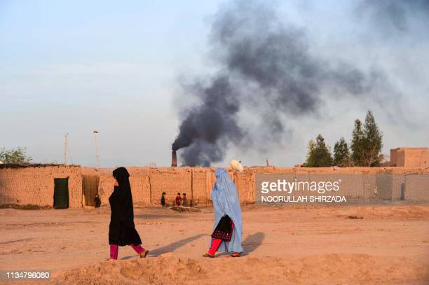 TOPSHOT In this photograph taken on April 3 Afghan women walk near a brick factory as smoke rises up in the sky from a chimney on the outskirts of...