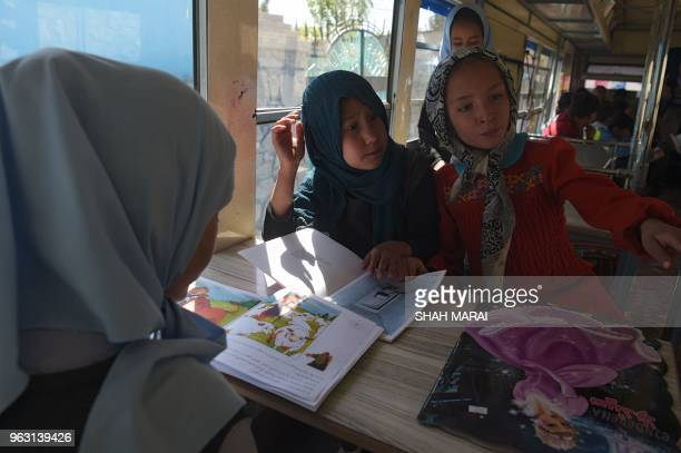 In this photograph taken on April 4 Afghan children read books in a mobile library bus in Kabul The door of the blue bus slides open and dozens of...