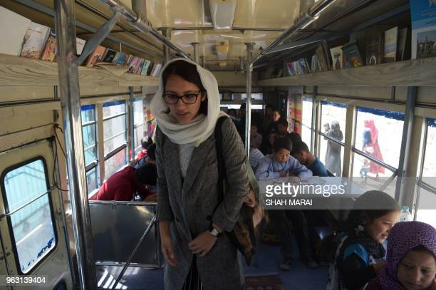 In this photograph taken on April 4 Freshta Karim walks inside the mobile library bus she launched in February as children read books in Kabul The...