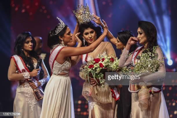 In this photograph taken on April 4 winner of Mrs. Sri Lanka 2020 Caroline Jurie removes the crown of 2021 winner Pushpika de Silva as she is...