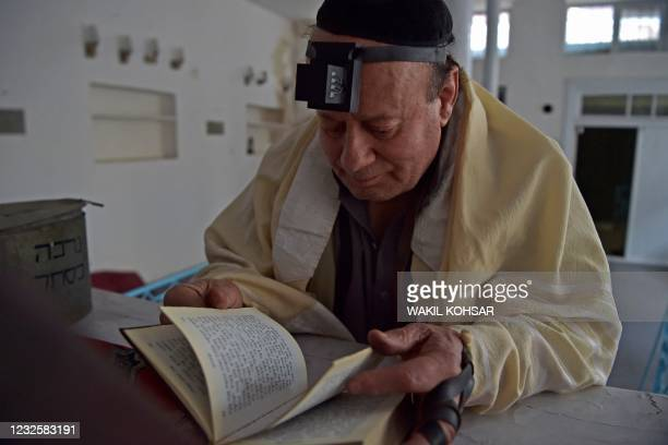 In this photograph taken on April 5 Afghan Jew Zebulon Simentov looks at the Torah scripture at synagogue, housed in an old building in Kabul. - For...