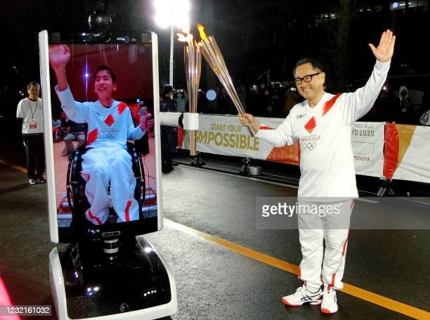 In this photograph taken on April 6, 2021 Toyota Motor Corp. President Akio Toyoda passes the olympic flame to Japanese disabled Shunsuke Suzuki via...