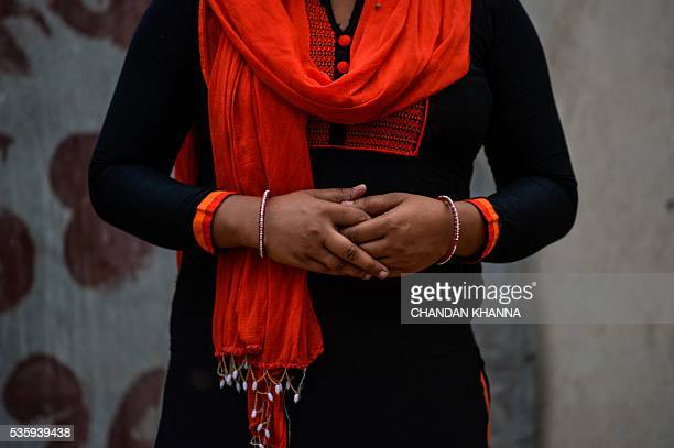 In this photograph taken on April 6 'Ragini' a victim of marital rape poses sitting outside near her home in New Delhi India has long suffered from...