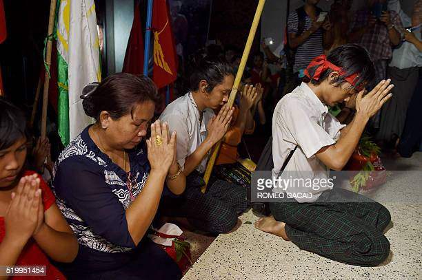 In this photograph taken on April 8 freed students and supporters pray at a memorial hall upon their arrival in Yangon. A Myanmar court on April 8...