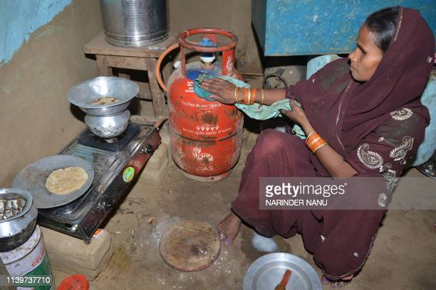 In this photograph taken on April 8 Indian women Reena Devi cleans a gas cylinder as she prepares food on a gas stove in Nisarpura village on the...