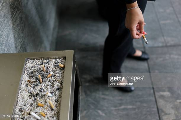 In this photograph taken on August 1 a Chinese woman smokes a cigarette in the Lujiazui Financial District in Pudong in Shanghai A wildly popular...