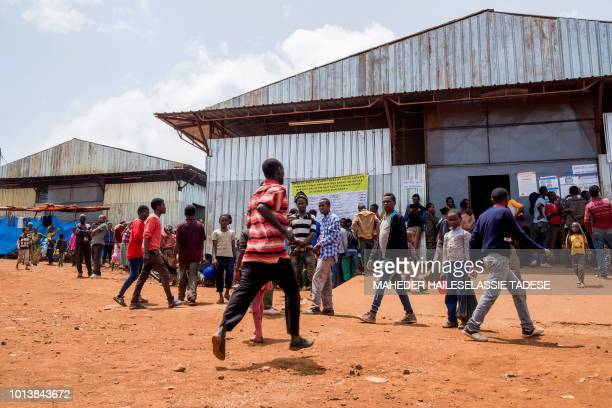 In this photograph taken on August 1 displaced Gedeo gather around temporary food distribution units in Dilla in the Gedeb area of Ethiopia...
