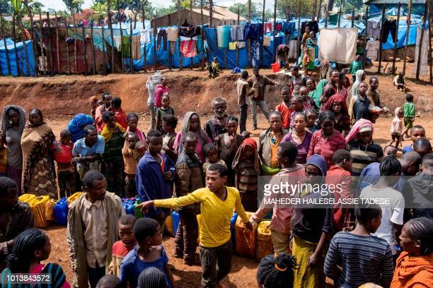 In this photograph taken on August 1 displaced Gedeo people wait in line with their containers looking for water at Kercha site West Guji in Ethiopia...