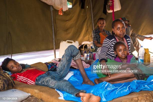 In this photograph taken on August 1 displaced woman Azaleche Beyene mother of seven sits with her children as they rest at a temporary shelter for...