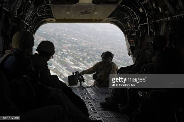 In this photograph taken on August 10 a US soldier sits in the rear of Chinook helicopter while flying over Kabul Fresh recruits to Afghanistan's...