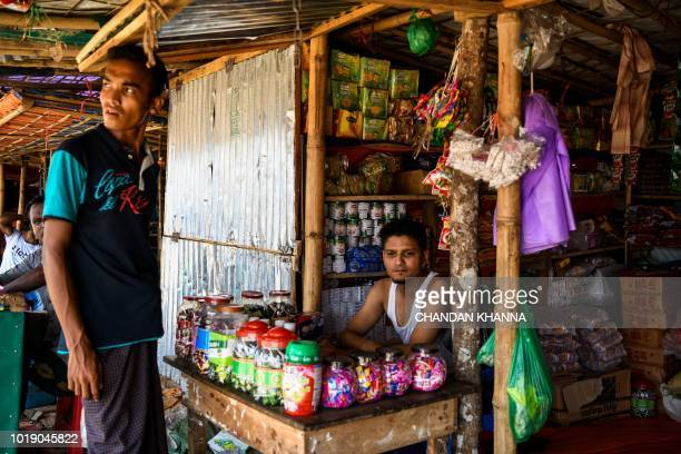 In this photograph taken on August 11 a Rohingya refugee trader sits in his makeshift shop as he waits for customers in the Thengkhali camp in Cox's...