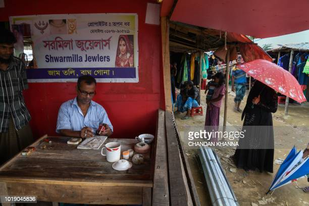 In this photograph taken on August 11 Bangladeshi gold trader Tapan Dhar repairs a gold ornament at his makeshift jewellery shop in the Thengkhali...