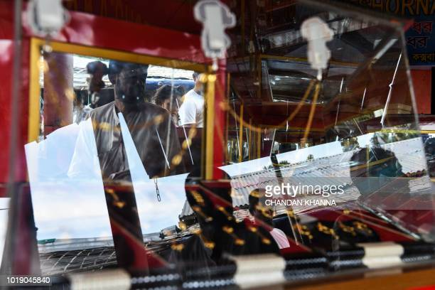 In this photograph taken on August 11 Rohingya refugees are reflected in a jewellery display shelf at a makeshift jewellery shop in the Thengkhali...