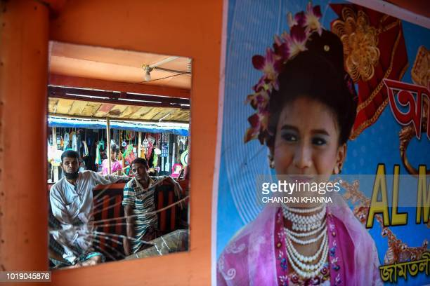 In this photograph taken on August 11 Rohingya refugees are seen in a mirror at a makeshift jewellery shop in the Thengkhali camp in Cox's Bazar The...