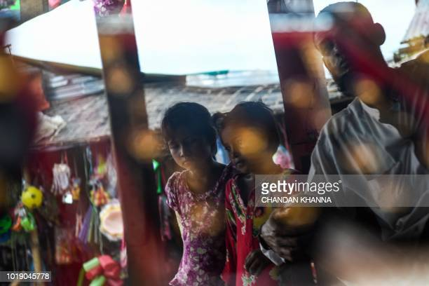 In this photograph taken on August 11 young Rohingya refugees are pictured by a jewellery display shelf at a makeshift jewellery shop in the...