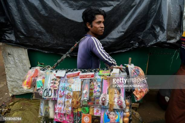 In this photograph taken on August 12 a Rohingya refugee carries various items to sell in the Kutupalong camp in Cox's Bazar The Bangladeshi district...