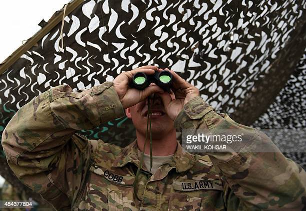 In this photograph taken on August 12 a US army soldier looks on with binoculars at Coalition forces Forward Operating Base Connelly in Khogyani...