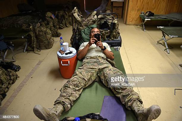 In this photograph taken on August 12 a US army soldier plays on a smartphone as he lies on a bed at coalition force Forward Operating Base Connelly...