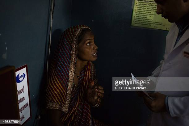 In this photograph taken on August 13 an Indian patient talks to a member of medical staff at the Dr Shroff Charity Eye Hospital Vision Centre in...