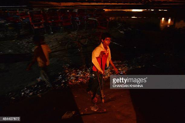 In this photograph taken on August 13 an Indian resident walks towards a temporary cinema theatre in New Delhi For 10 INR cyclerickshaw pullers...