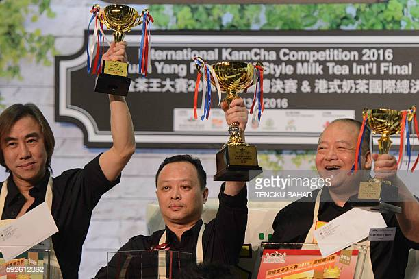 In this photograph taken on August 13 winner of the Hong Kong Style Milk Tea international final, Chan Chi-Ping from Hong Kong , holds up his trophy...