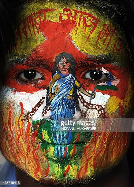 In this photograph taken on August 14 a student with social message and the colours of the Indian tricolour painted on his face poses on the eve of...