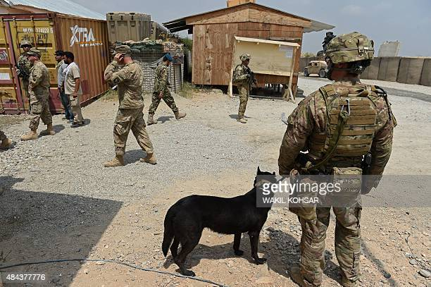 In this photograph taken on August 14 a US army soldier and military dog keep watch as Afghan National Army soldiers walk through coalition force...