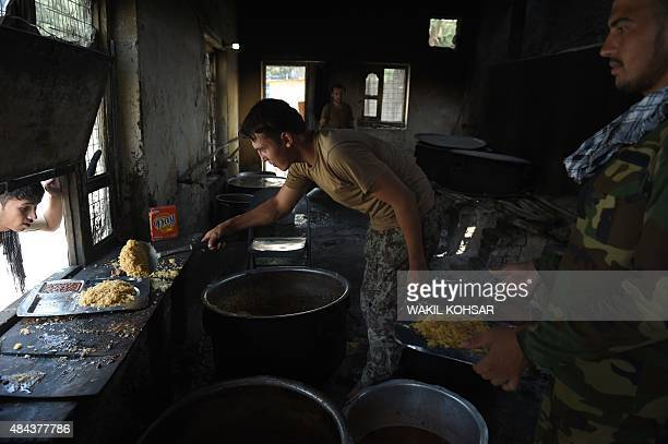 In this photograph taken on August 14 Afghan National Army soldiers are served lunch at a kitchen inside a base in the Khogyani districtin the...