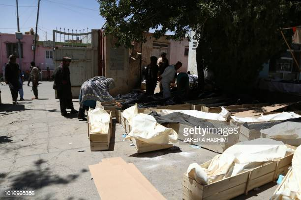 In this photograph taken on August 14 Afghan residents stand next to coffins containing corpses at a roadside following clashes with Taliban fighters...