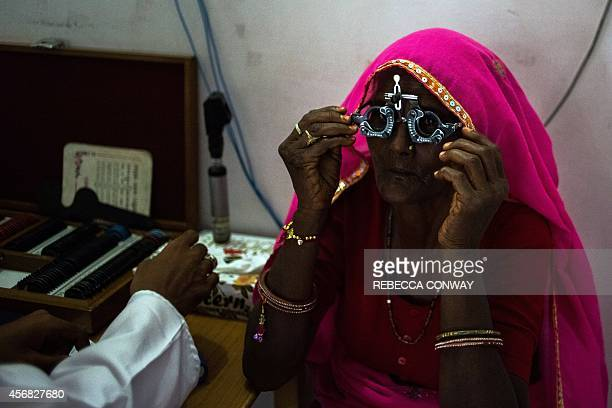 In this photograph taken on August 14 an Indian patient adjusts a pair of glasses used to test eyesight during an examination at the Dr Shroff...