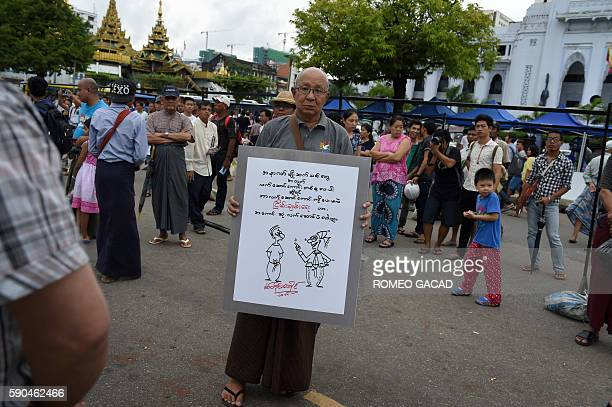 In this photograph taken on August 14 senior Myanmar cartoonist Pyit Taing Htaung poses with his social commentary political cartoon at the end of a...