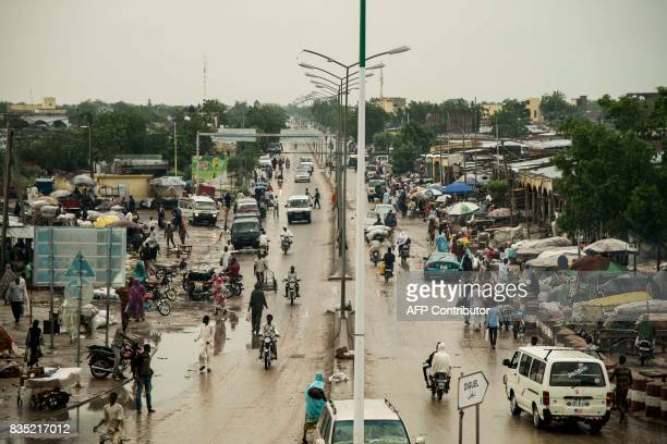 In this photograph taken on August 15 pedestrians walk in a market area of the Chadian capital of N'Djamena / AFP PHOTO / Xaume Olleros